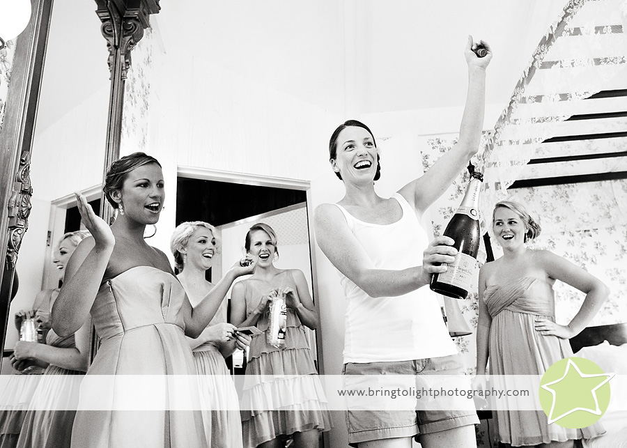 bride pops a bottle of champagne for her bridesmaids